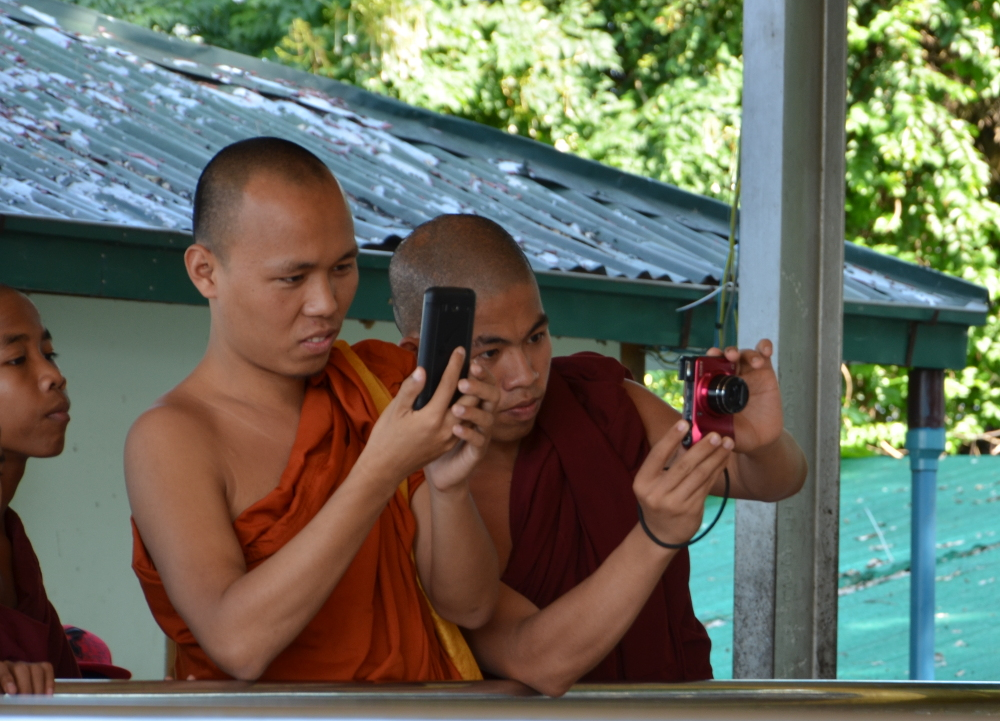The monks are eager to take photos of the holy snakes and of each other with the snakes