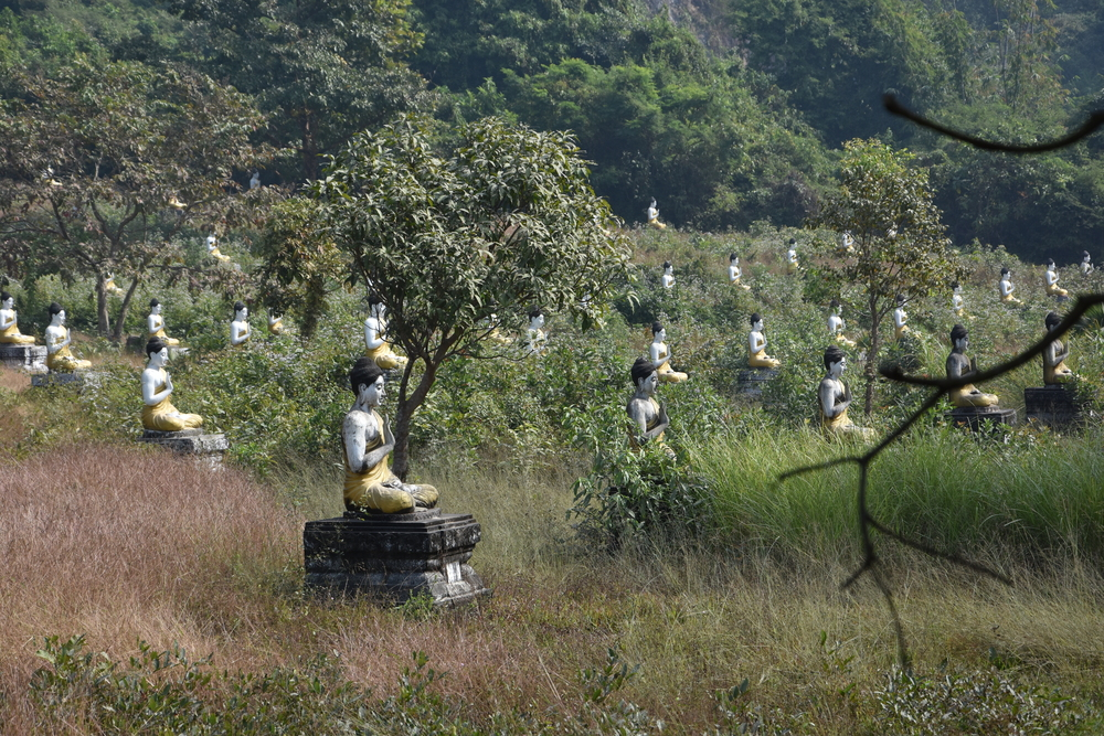1121 Buddha statues are placed in the forrest beneath a steep mountain